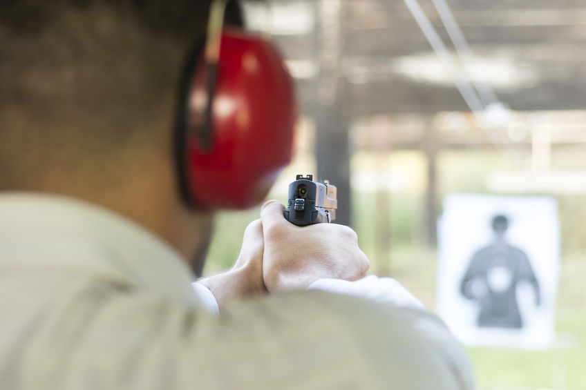 Man with ear protection on aiming handgun at target