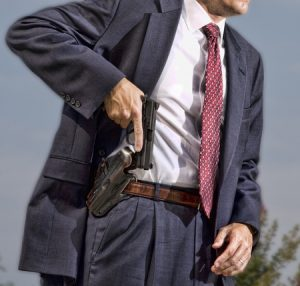 man in suit pulling his gun out of the holster