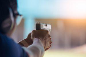 man pointing handgun at target