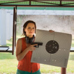 A woman at a shooting range with gun and target